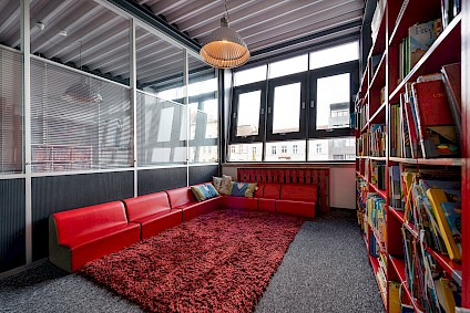 The Picasso group reading room of with a red corner sofa, teddy carpet and a whole wall full of books