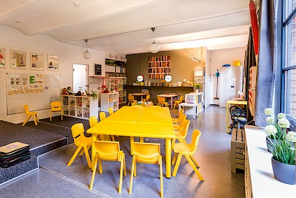 The cozy Einstein group room with yellow accents and lots of science to be explored