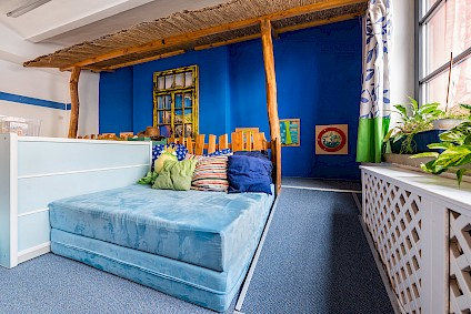 A large mattress and many colorful cushions in the Olympia room invite you to relax