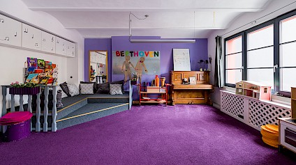 The music corner in the Beethoven room with fluffy violet carpets, drums, a piano and other instruments