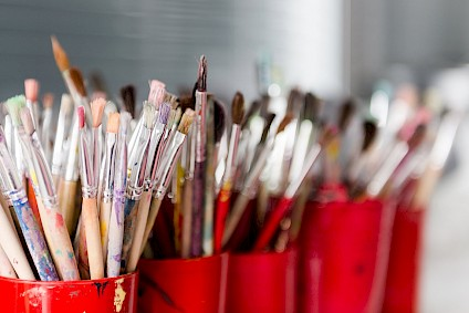 Countless brushes in all sizes and shapes, in red cups, of course